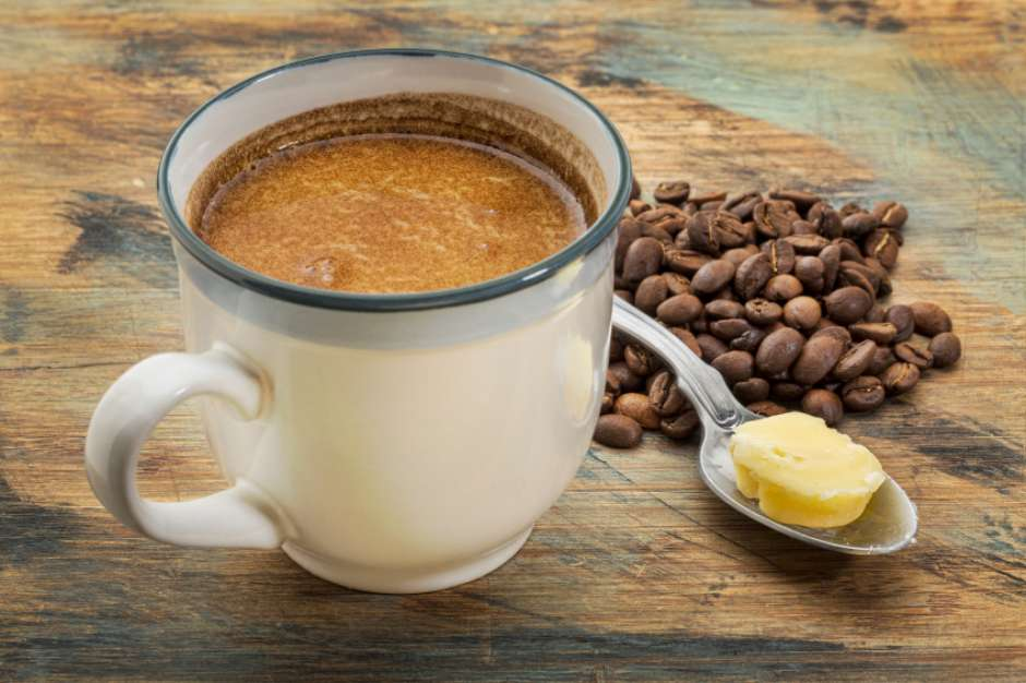 a cup of fresh fatty coffee with butter and coconut oil - ketogenic diet concept
